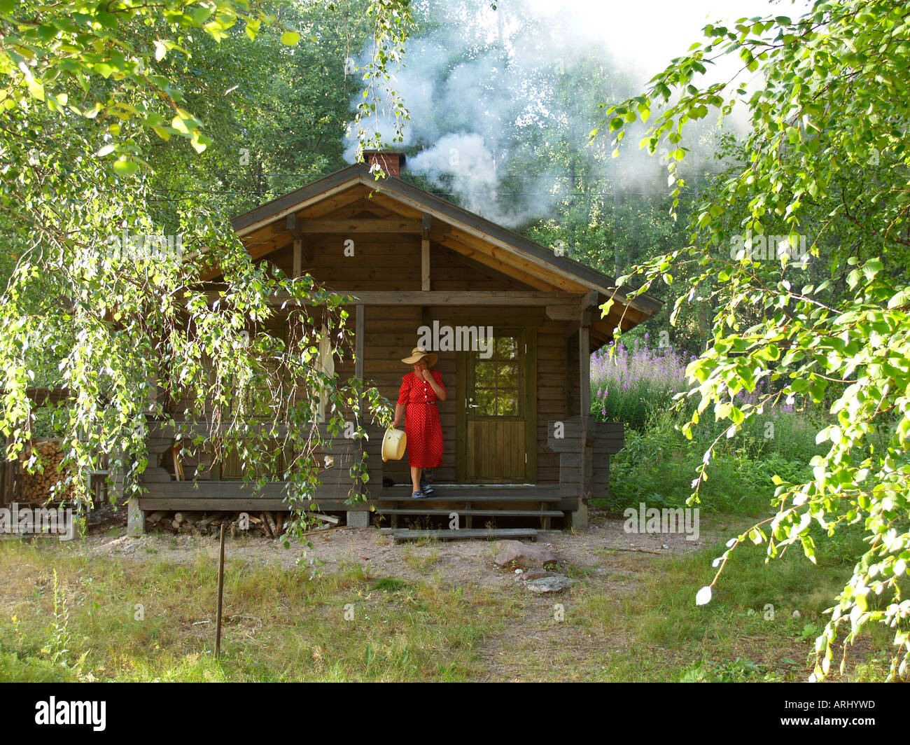 reeking sauna by heating a timber sauna in the nature in Finland - Stock Image