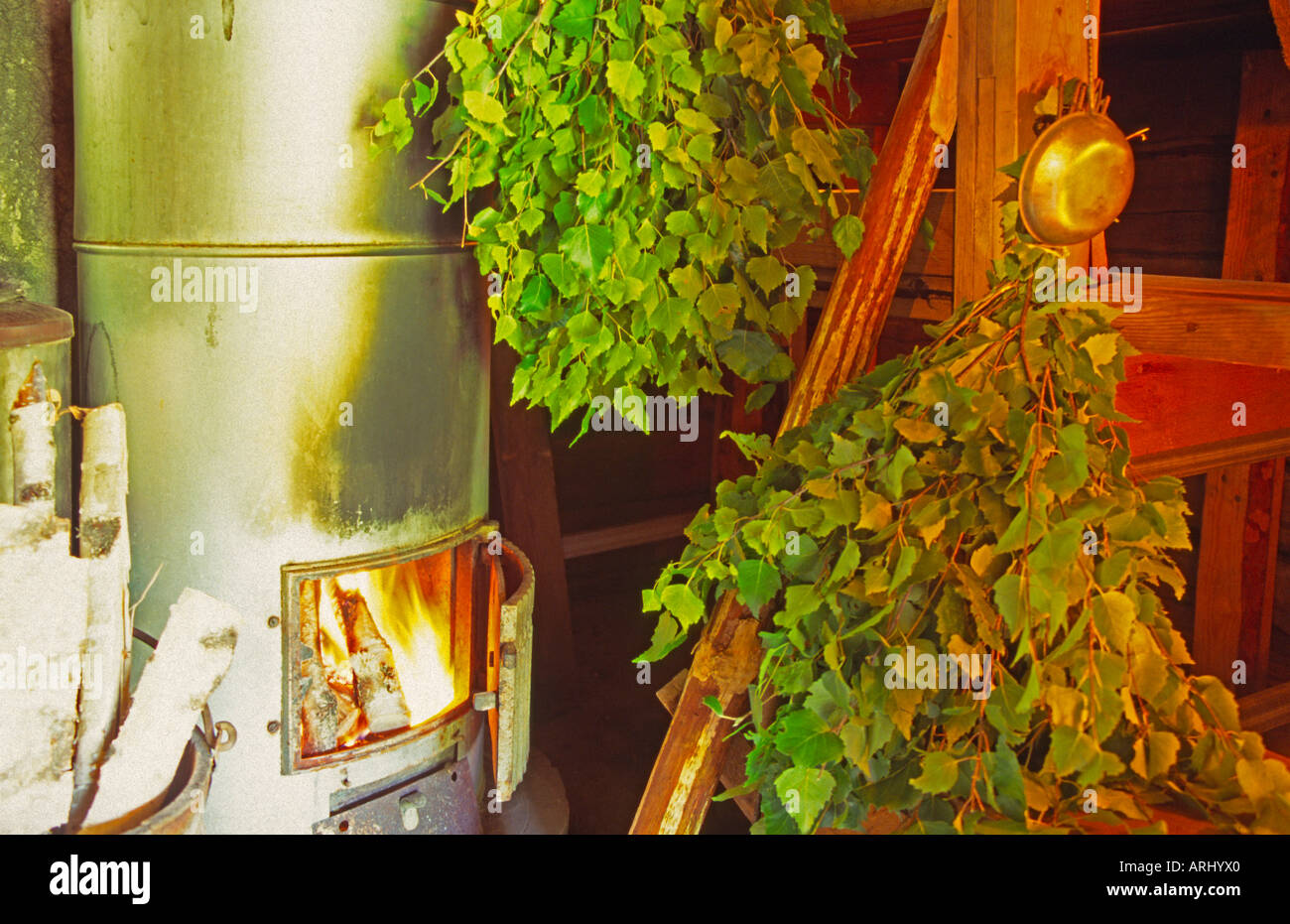 old sauna oven with fire two tufts of branches of birch in a sauna in Finland - Stock Image