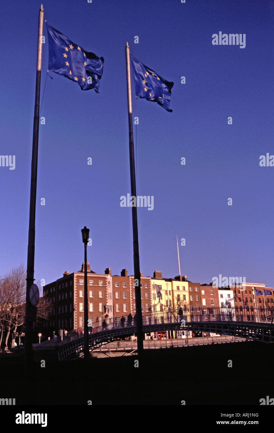 Dublin Ireland European Union flags fly by the Ha Penny Bridge over the River Liffey and Bachelor s Walk - Stock Image