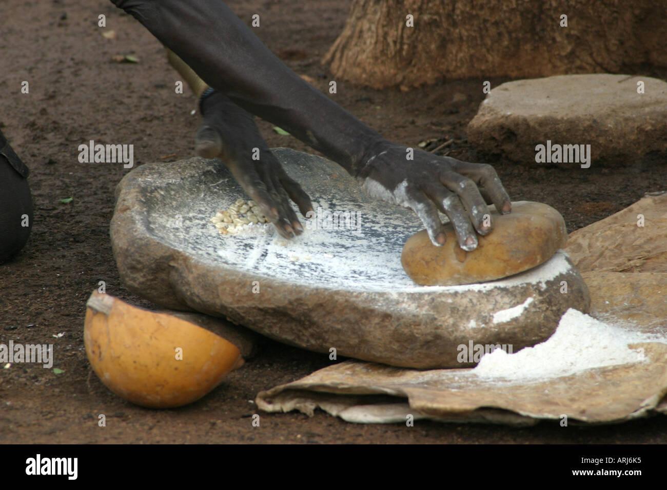 Toposa woman grinding sorghum on grindstone, Sudan - Stock Image