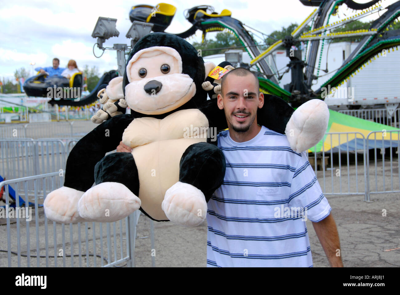 Adult male wins a large stuffed animal at the Michigan State Fair Held at Detroit Michigan MI - Stock Image
