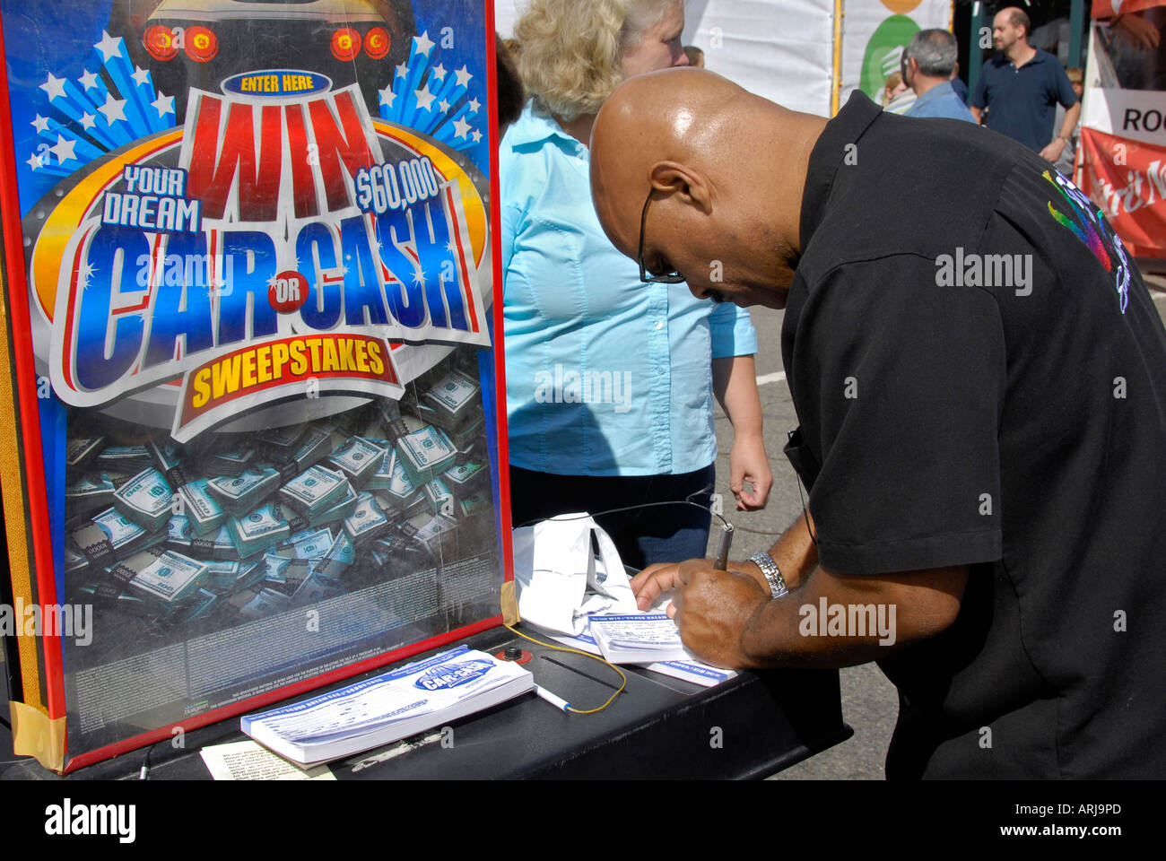 Men fill out forms and enter a chance game of sweepstakes - Stock Image