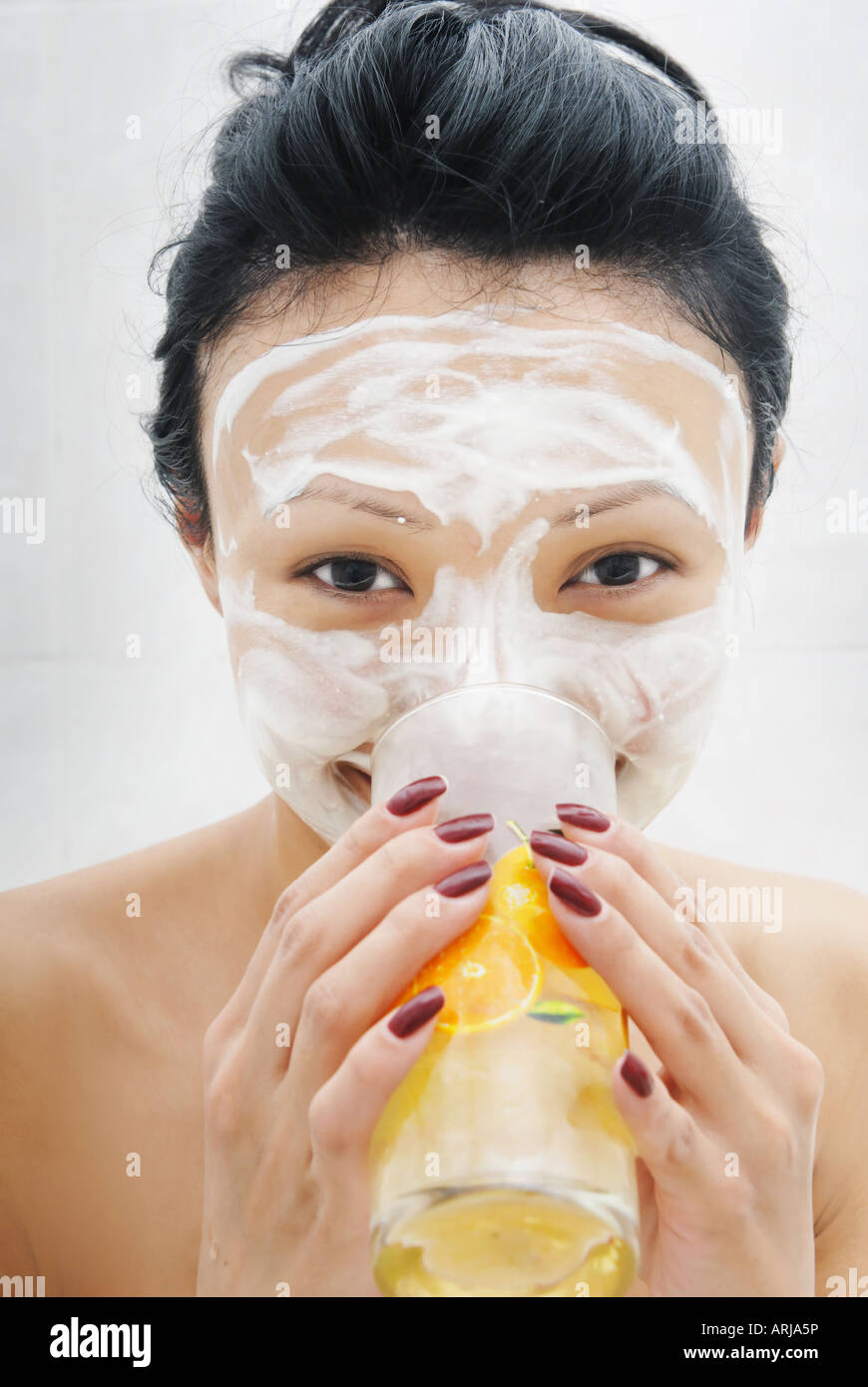 Drinking smiling woman with beauty mask Stock Photo