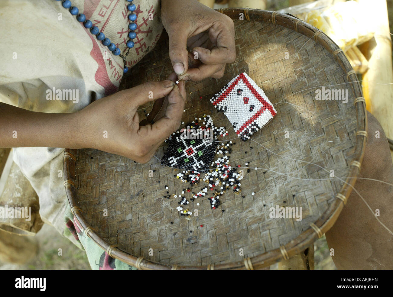 A Mangyan girl makes a cell phone case out of beads in the mountains of Oriental Mindoro, Philippines. - Stock Image
