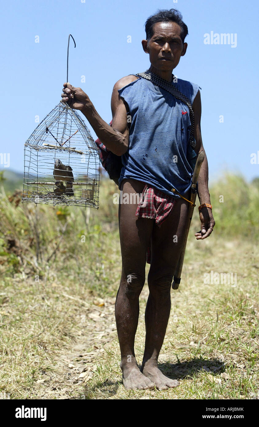 A Mangyan man carries a bird he trapped back to his village in the mountains of Oriental Mindoro, Philippines. - Stock Image