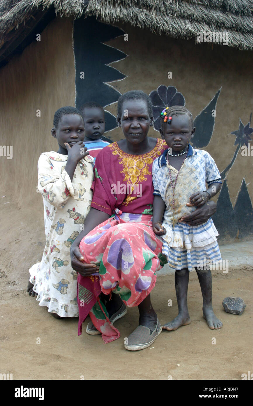 Dinka woman with her children in front of mud house, Sudan - Stock Image