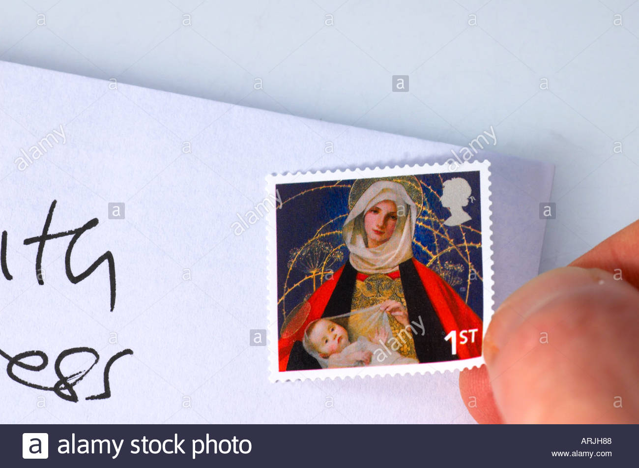 Placing a Christmas first class stamp on a envelope - Stock Image