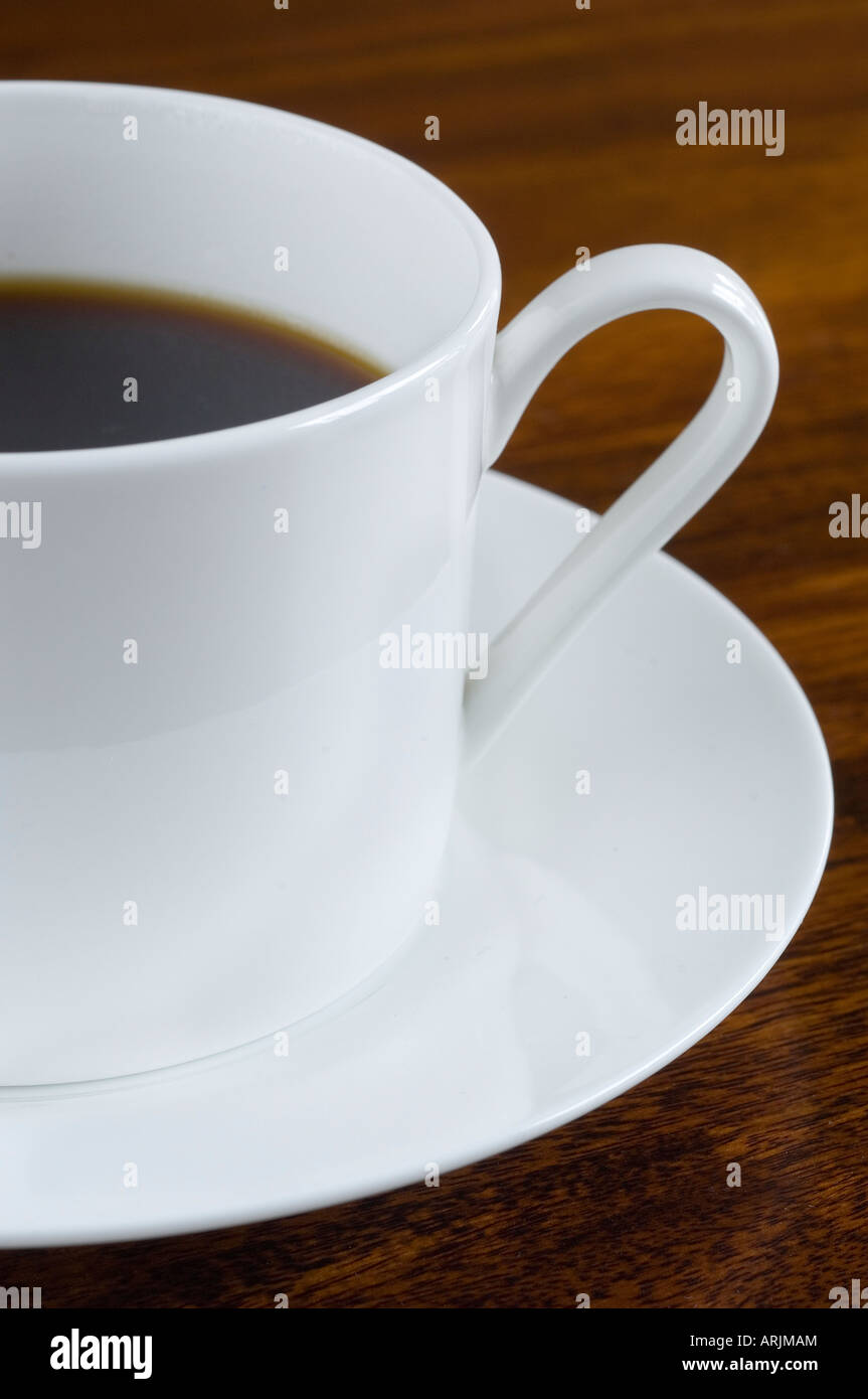 A porcelain cup of freshly brewed and poured Coffee on a white saucer stood on a dark wood table - Stock Image