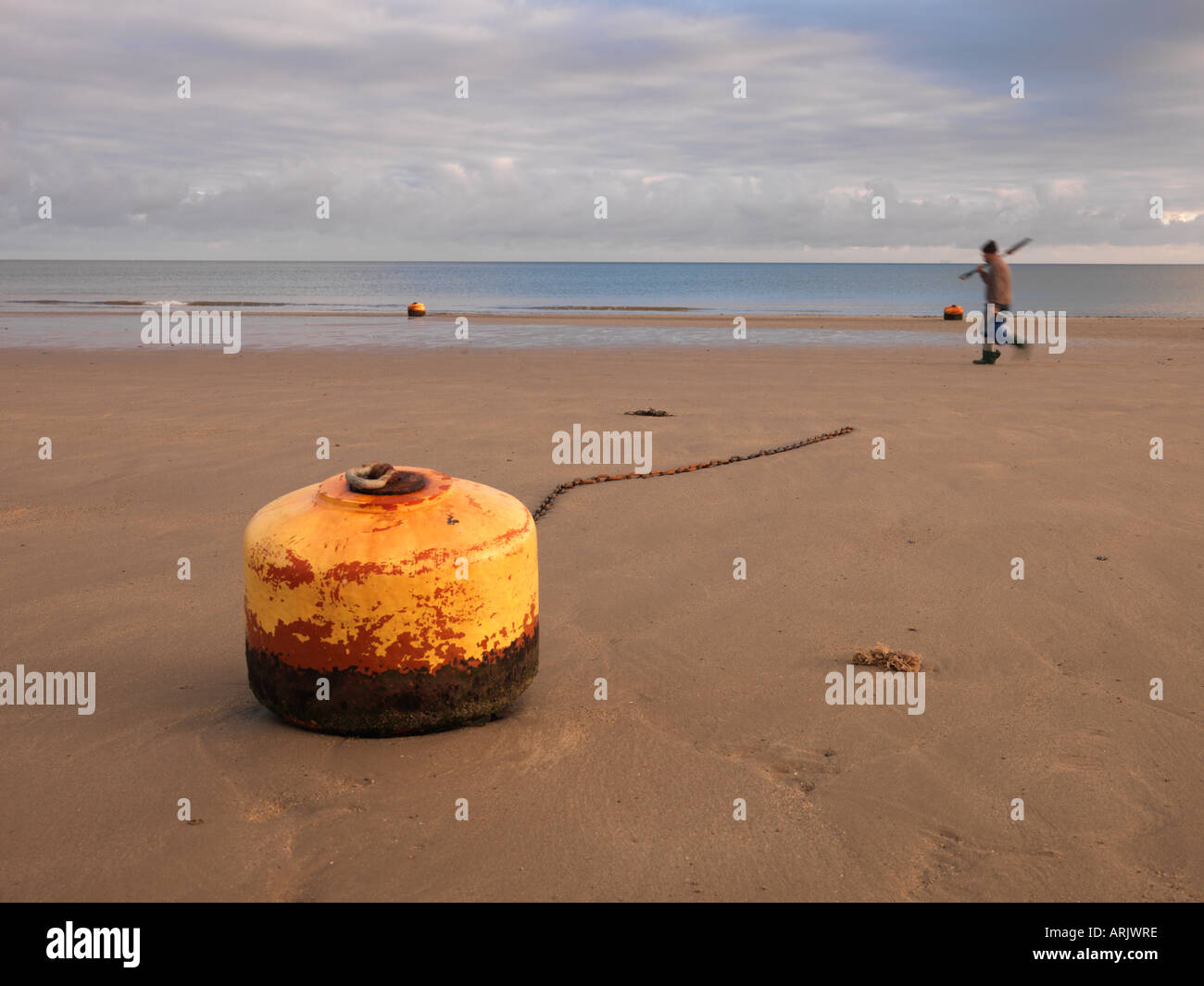 Man walking past buoy and chain on beach, Rhos-on-Sea, Wales, Summer 2006 - Stock Image