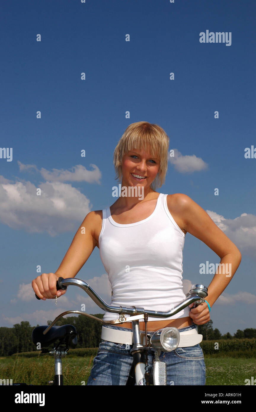 junge blonde Frau mit Fahrrad - young blonde woman with bike Stock Photo