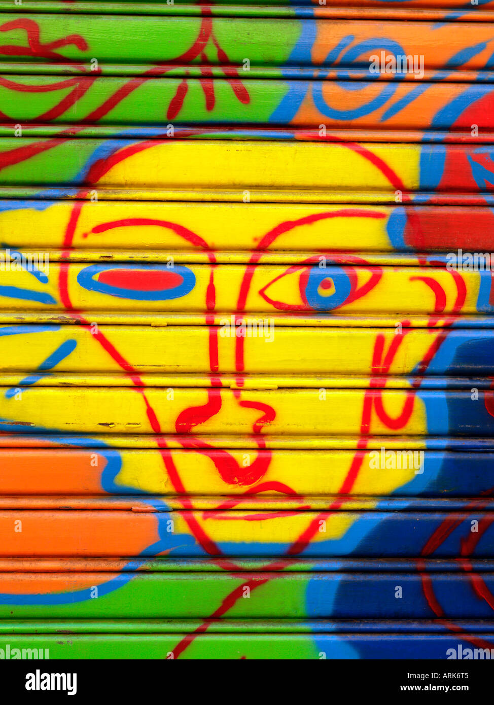 bizarre yellow face painted on shop security shutters - Stock Image