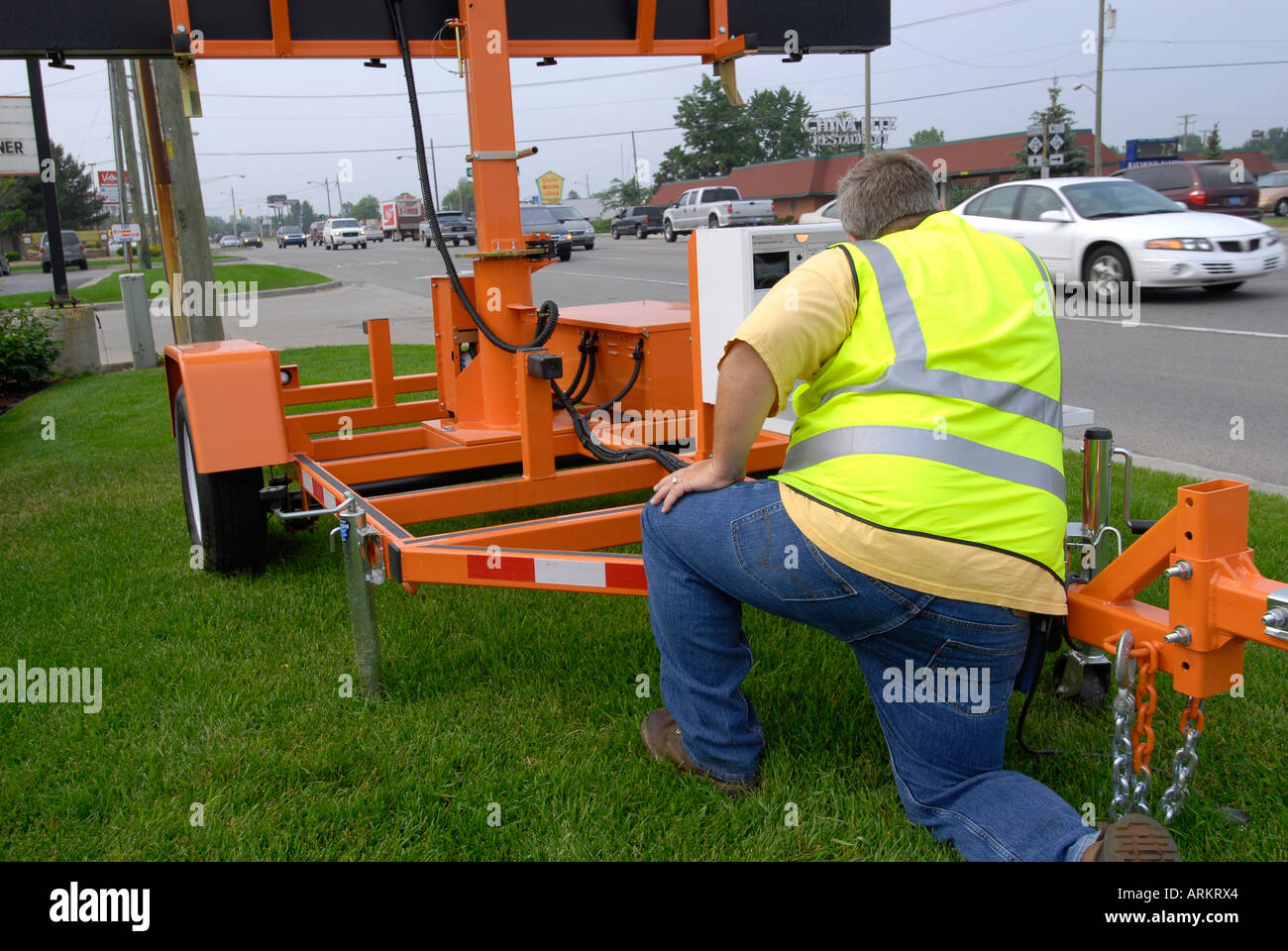 County road commission worker programs a sign for oncoming traffic - Stock Image