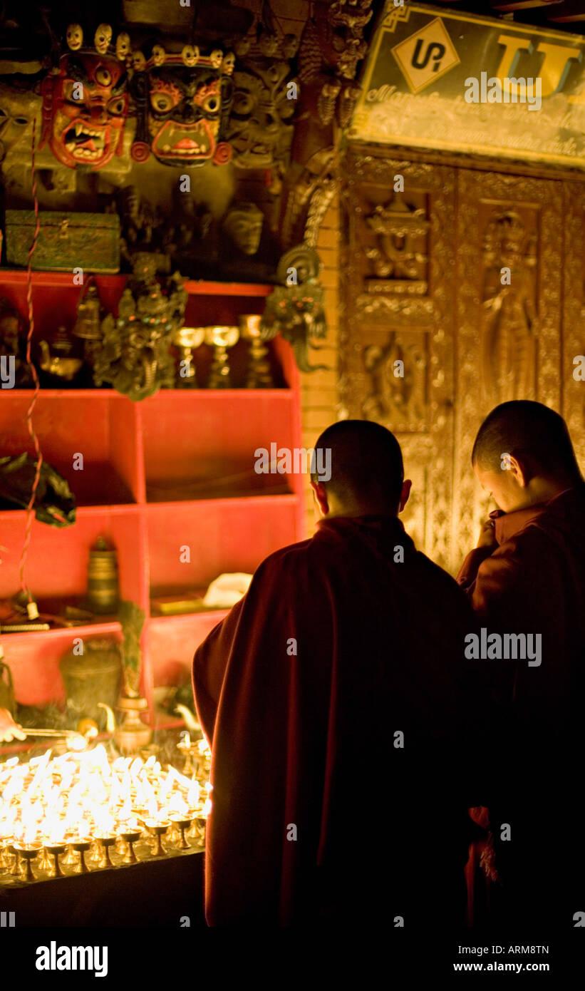Monks light butter lamps on an auspicious night, watched by two fearsome masks, Boudha stupa, Bodhnath, Kathmandu, - Stock Image