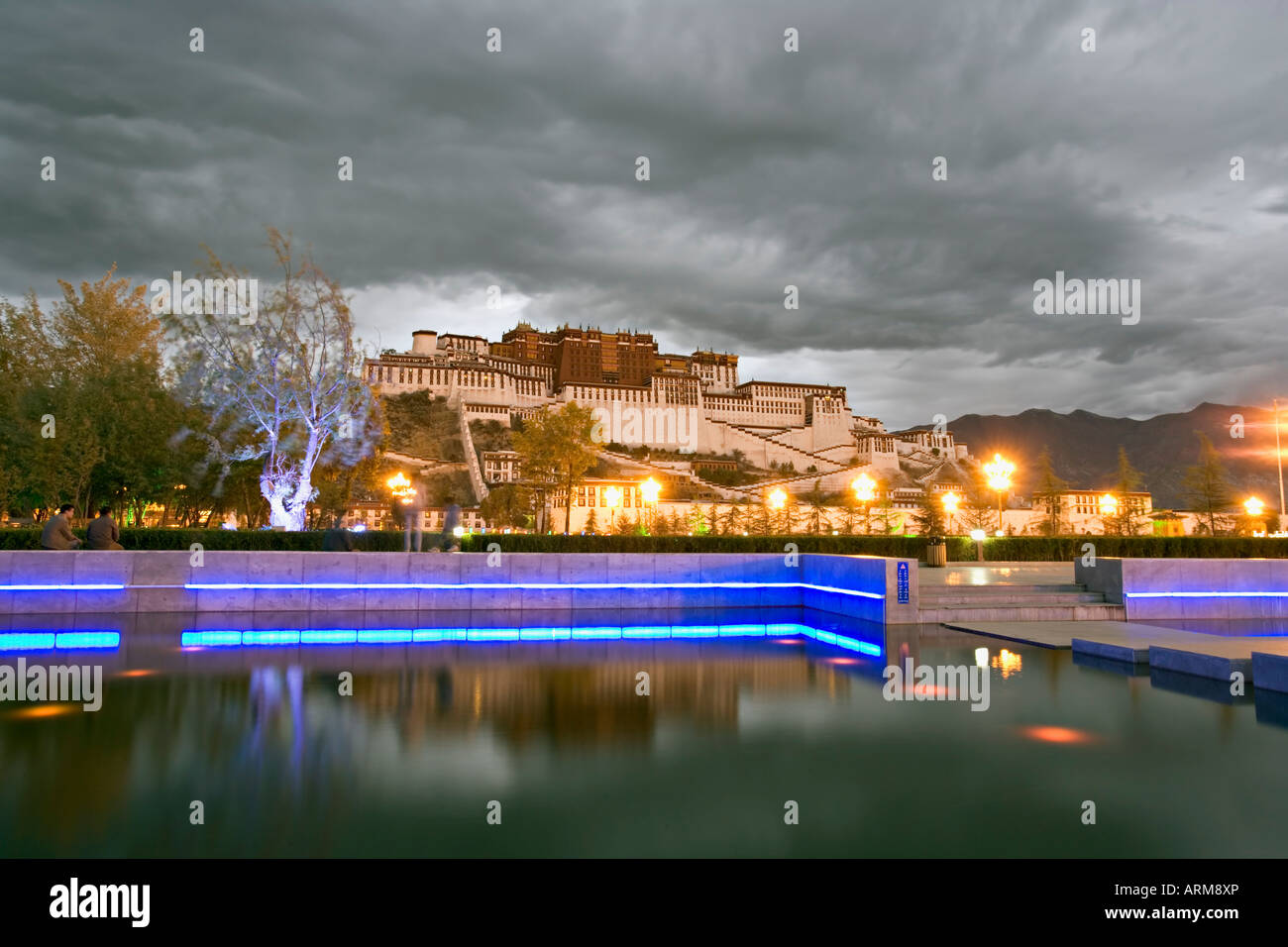 Water feature in front of the Potala Square lit up with neon blue lights in early evening, Lhasa, Tibet, China, - Stock Image