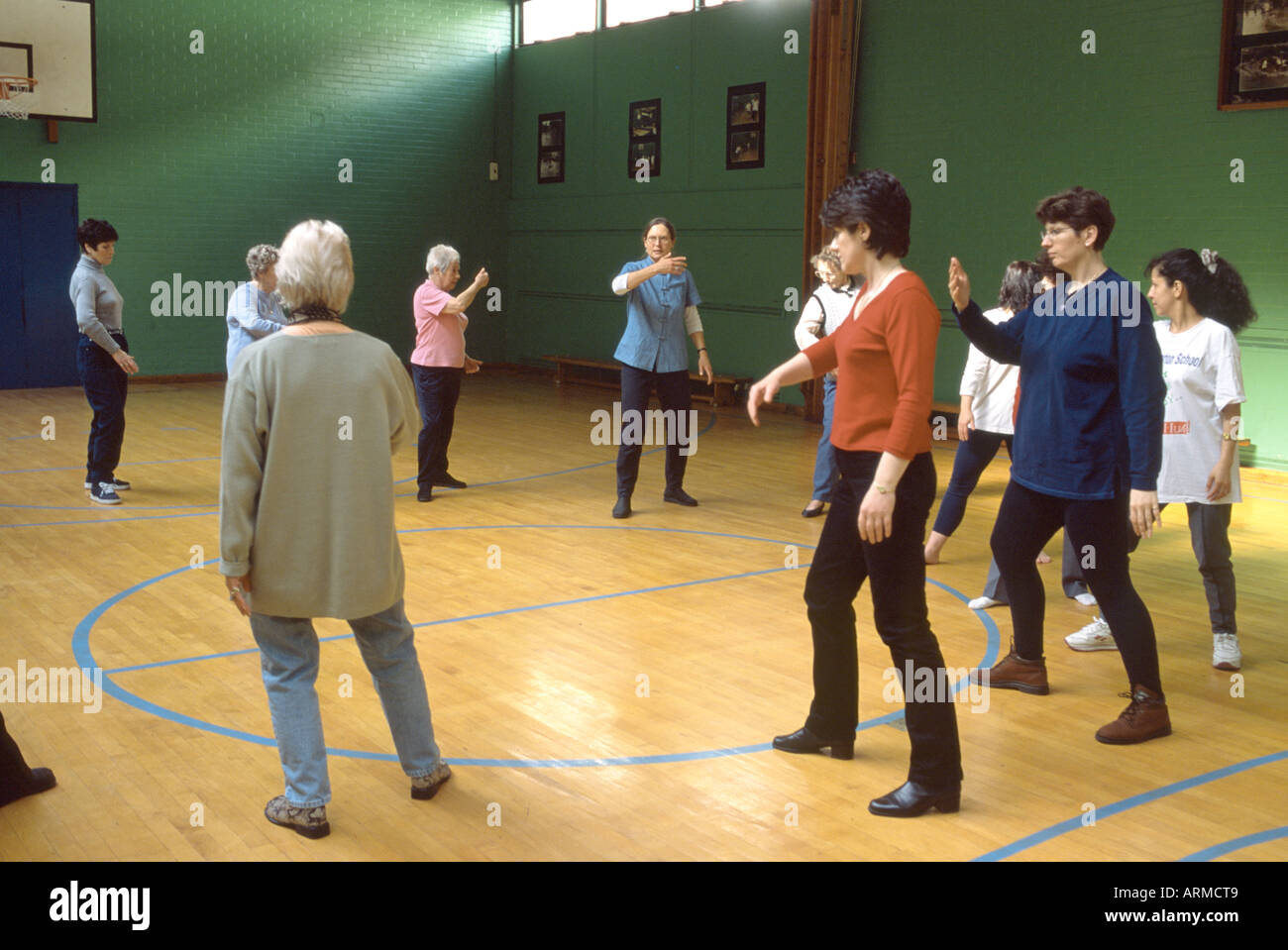 Tai chi class held in community gym - Stock Image