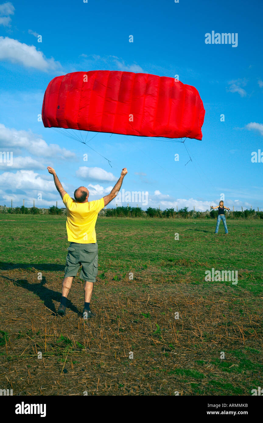Man launches a large kite on a South Wales hillside - Stock Image