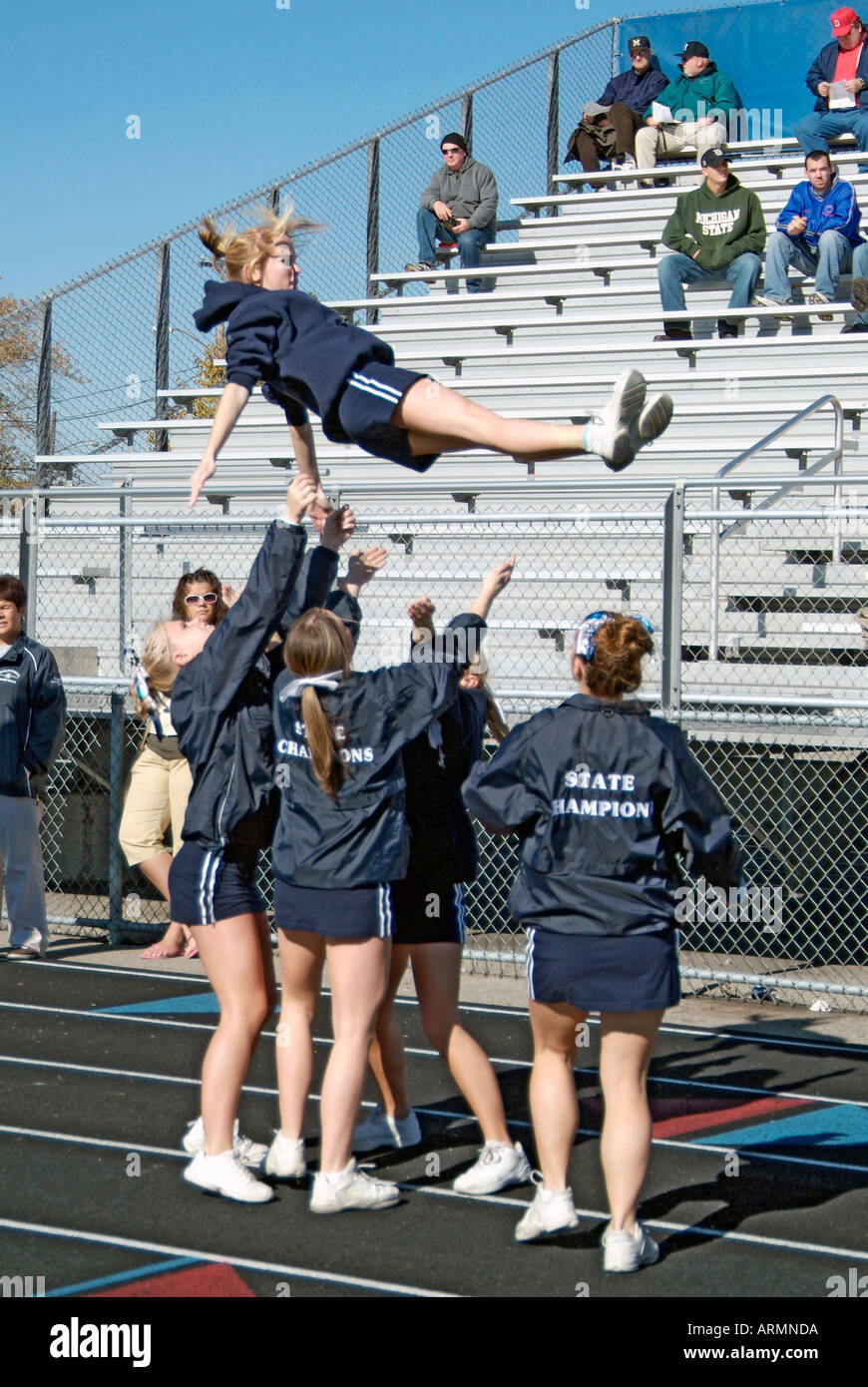 High School cheerleaders perform complicated and sometimes dangerous maneuvers during presentation at a football game - Stock Image