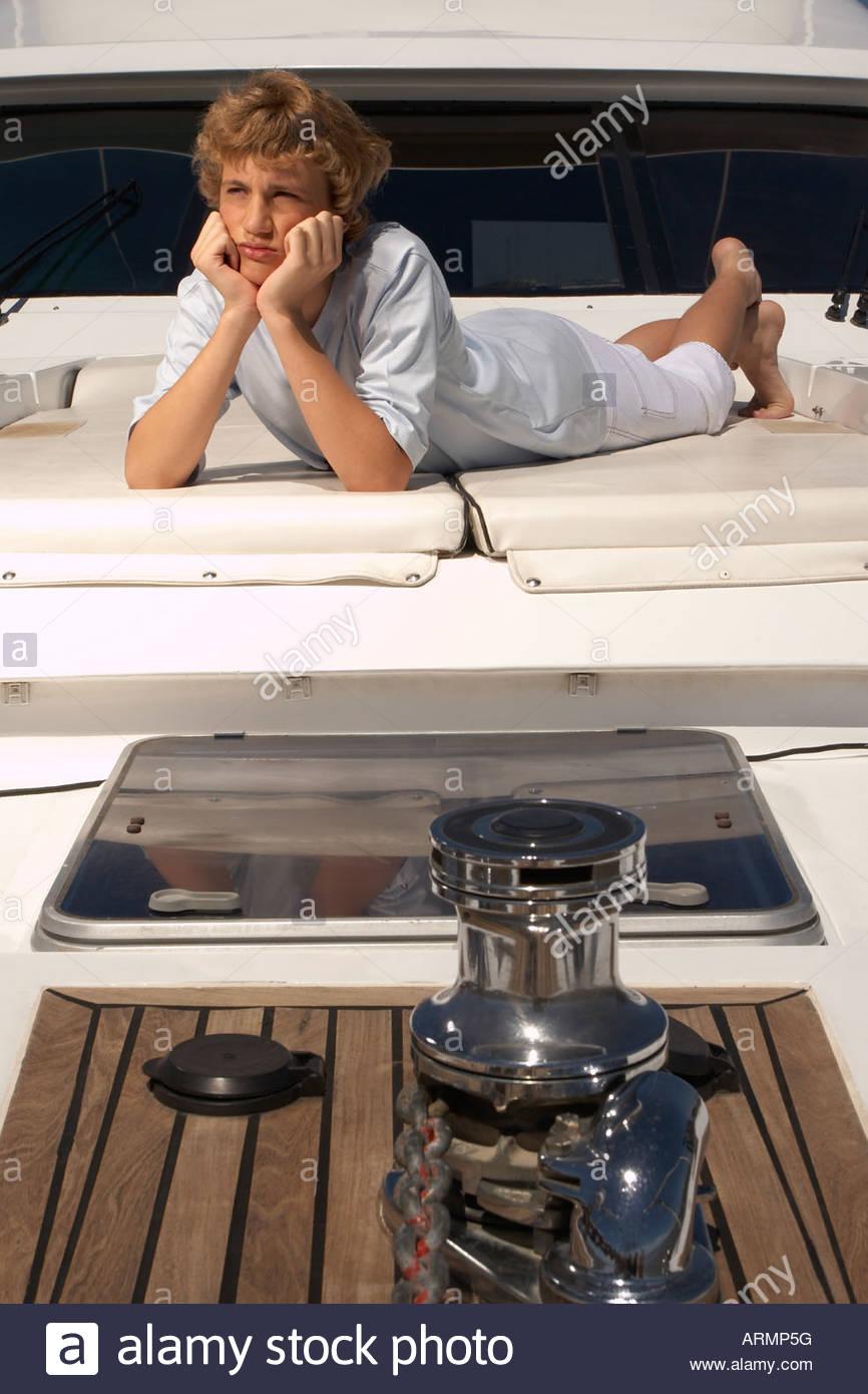 Teenage boy relaxing on boat - Stock Image