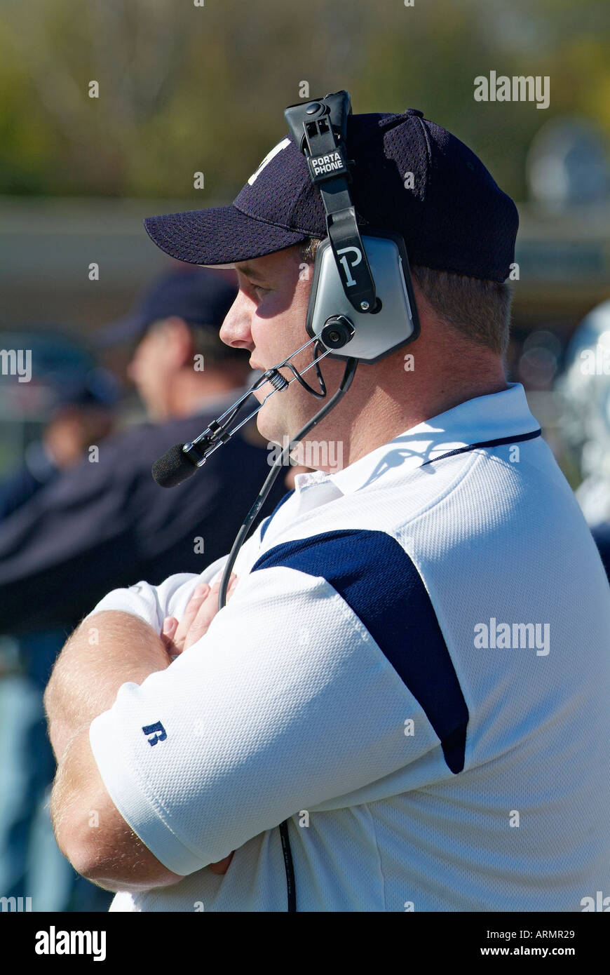 High school football coach communicate with other coaches by way of wireless headphone use - Stock Image