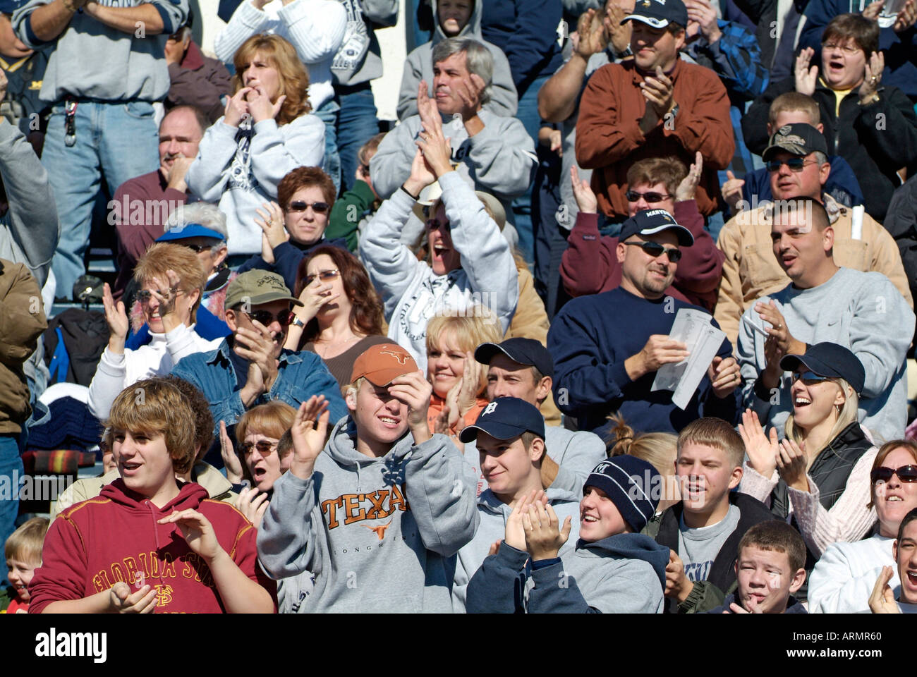 Crowd of people friends and family cheer and support a high school football team - Stock Image