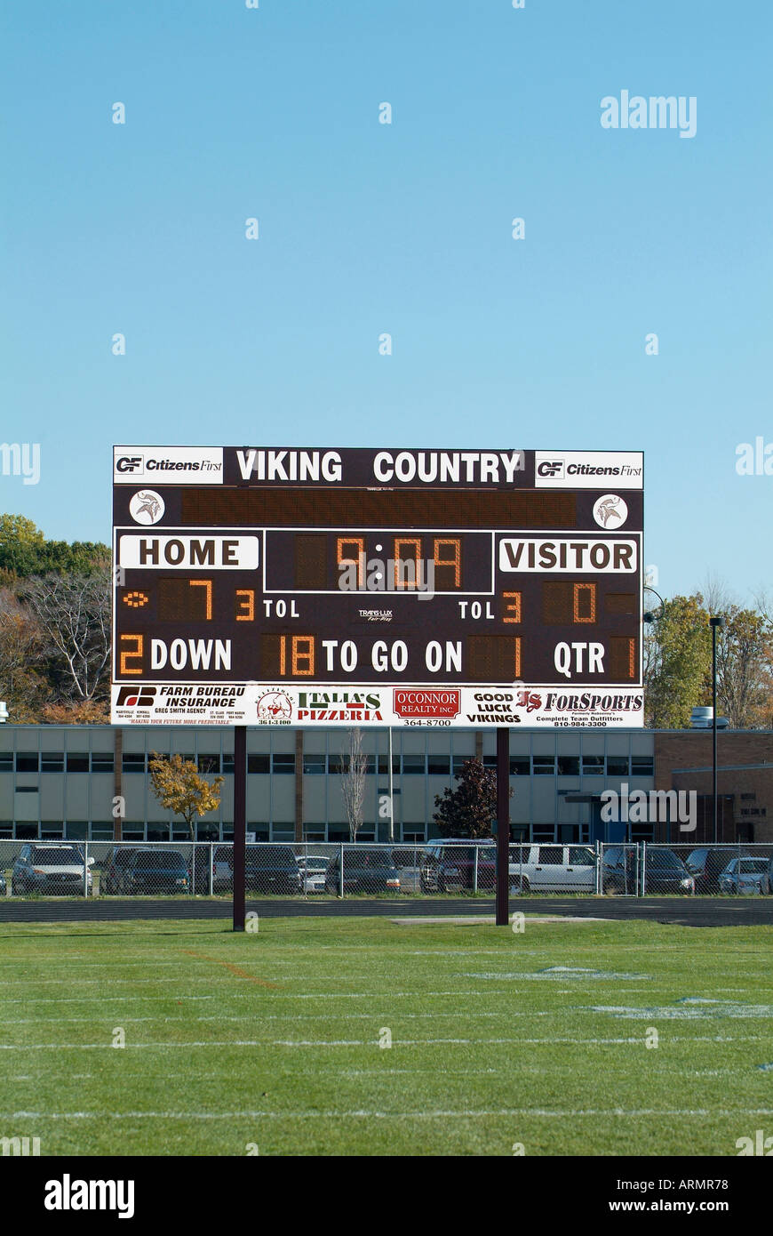 Football game with scoreboard indication the score and time left in a period - Stock Image