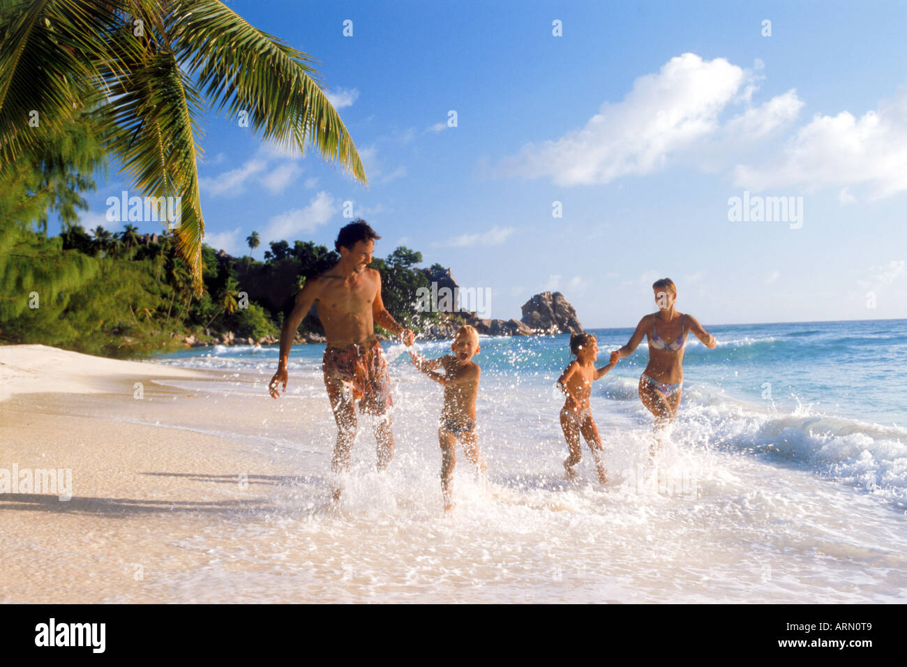 Family of  four running through shore waves on La Digue Island in Seychelles Stock Photo