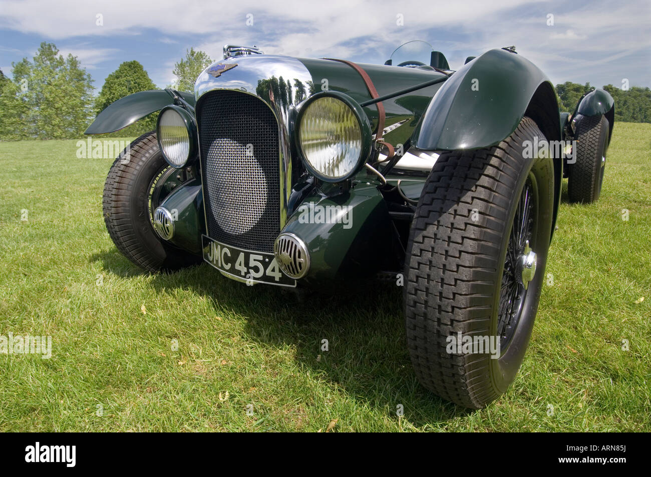 A close up of the front of a historic British racing green 1939 Lagonda V12 Le Mans motor car stood on grass - Stock Image