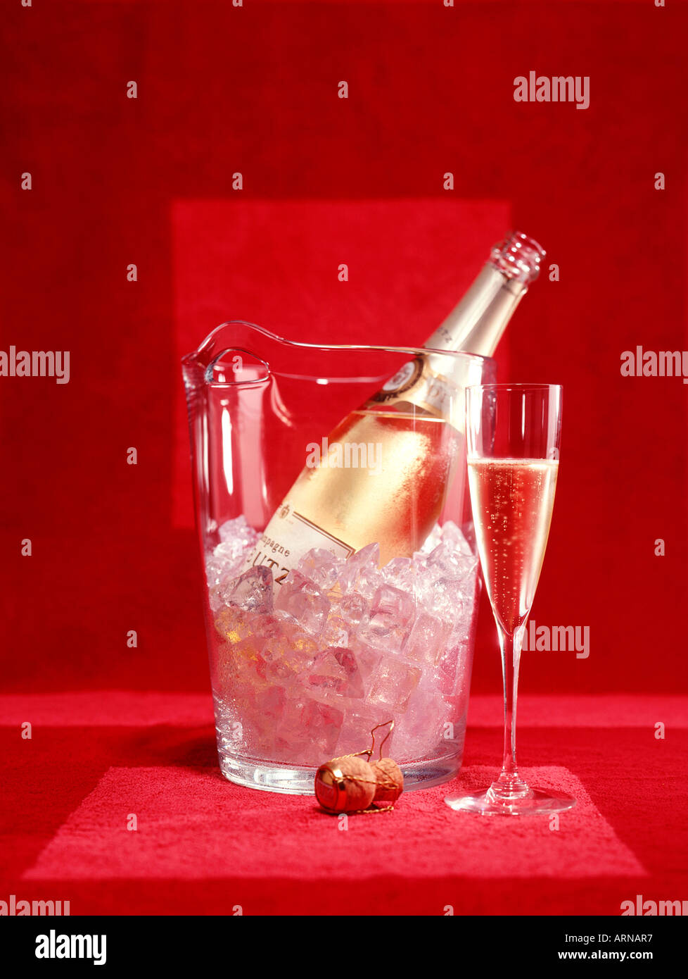 Champagne bottle on ice with champane flute Stock Photo