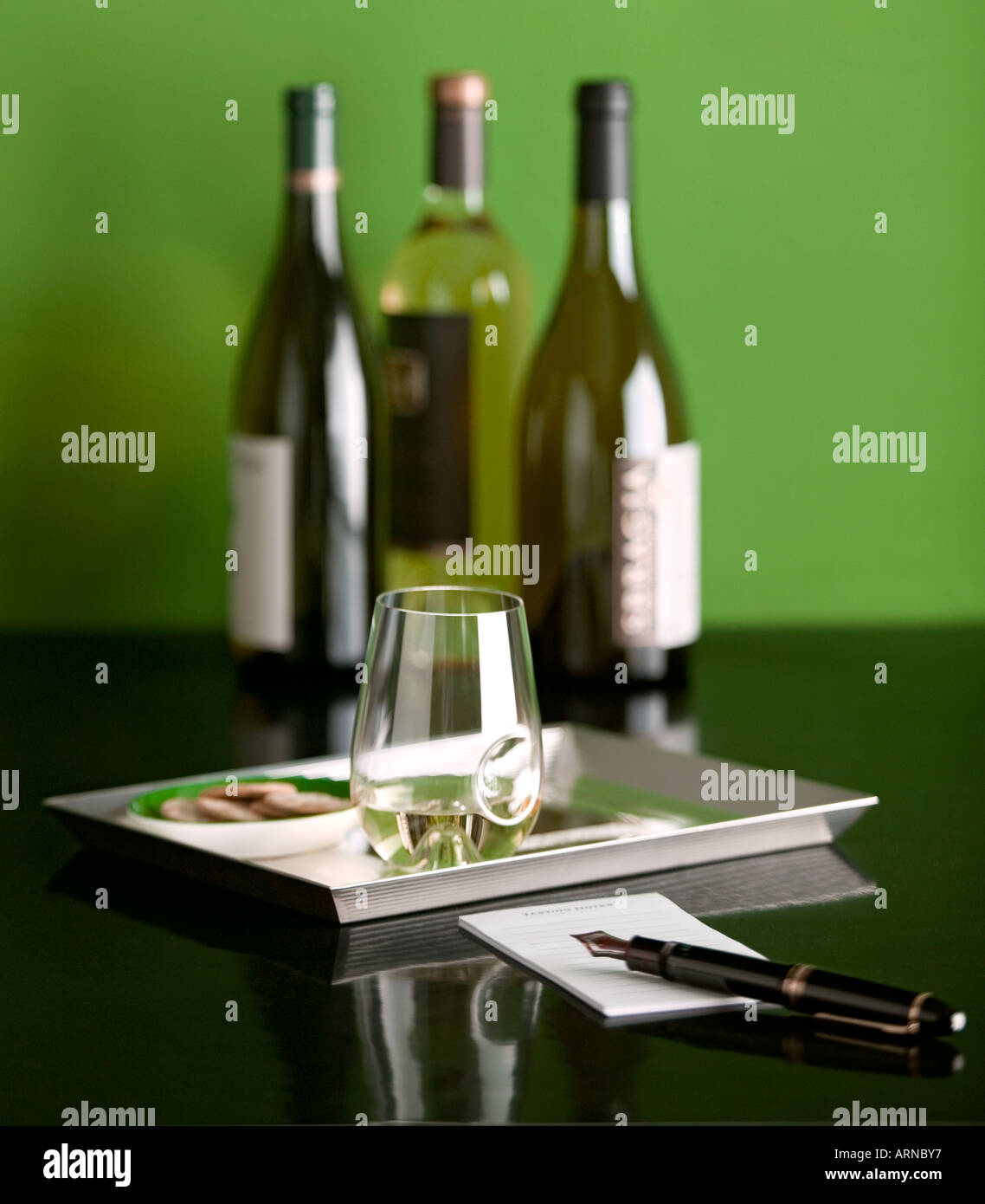 Wine tasting glass with crackers note pad pen and 3 bottles of wine Stock Photo