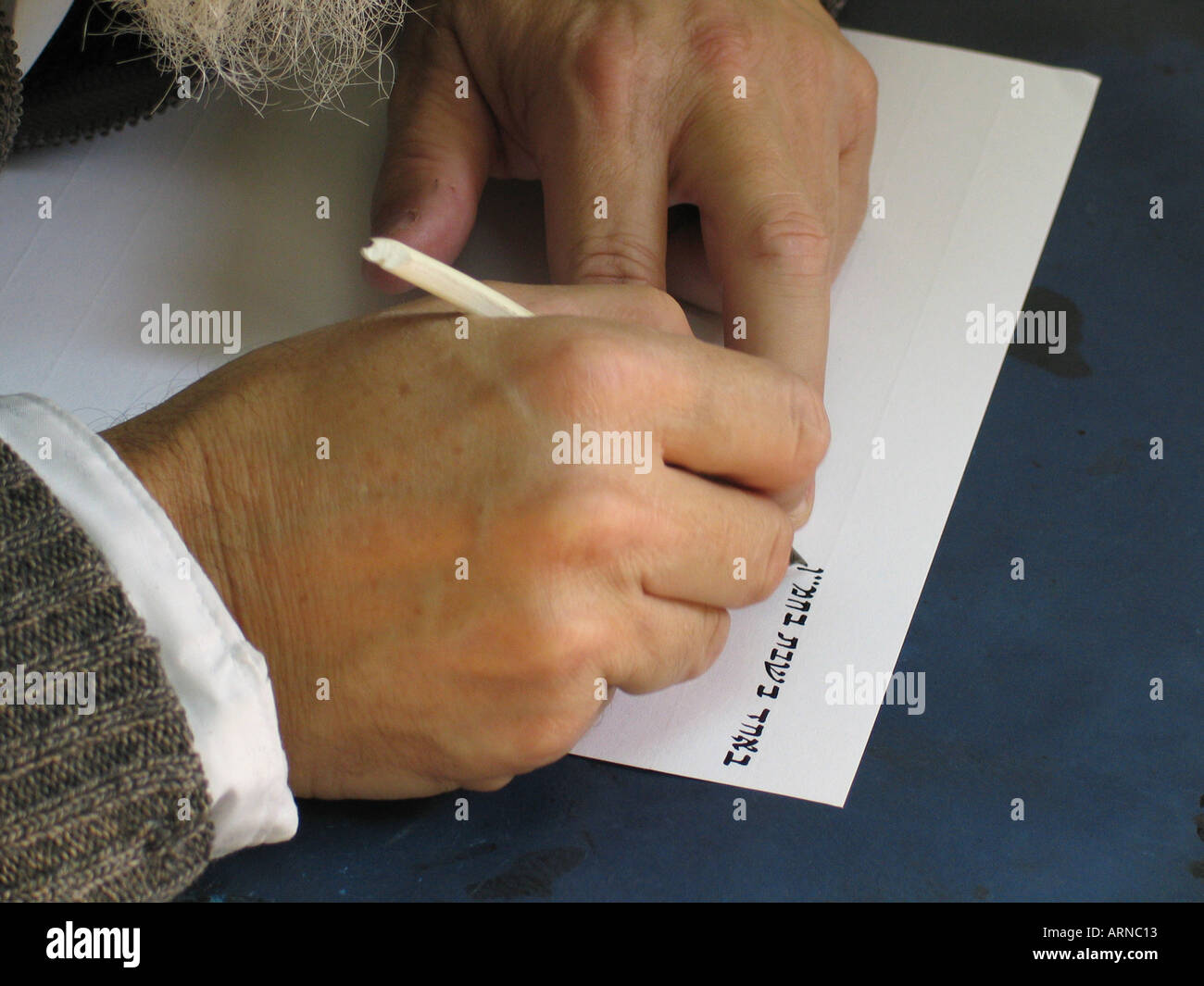 Calligrapher writing traditional Jewish divorce document on parchment - Stock Image