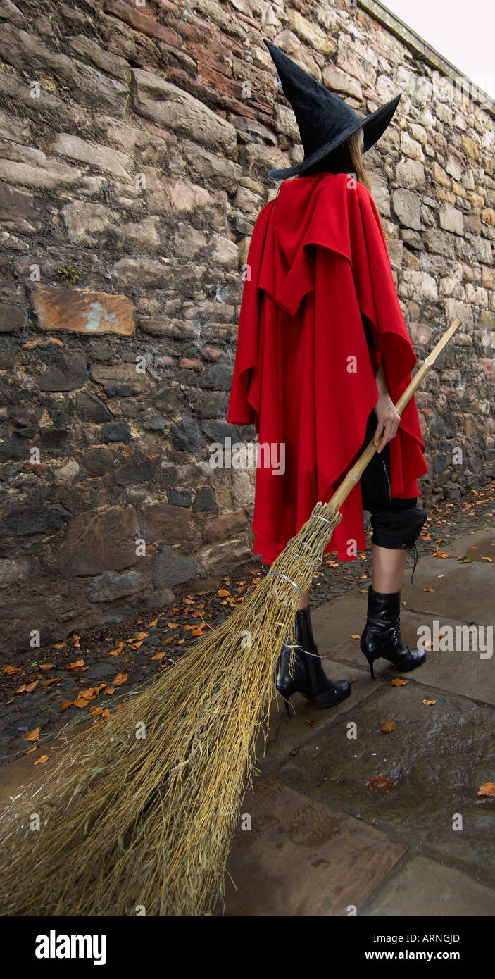 Rear view of a young woman wearing a red cape and a witch hat dragging a broomstick walking in a solitary alley - Stock Image