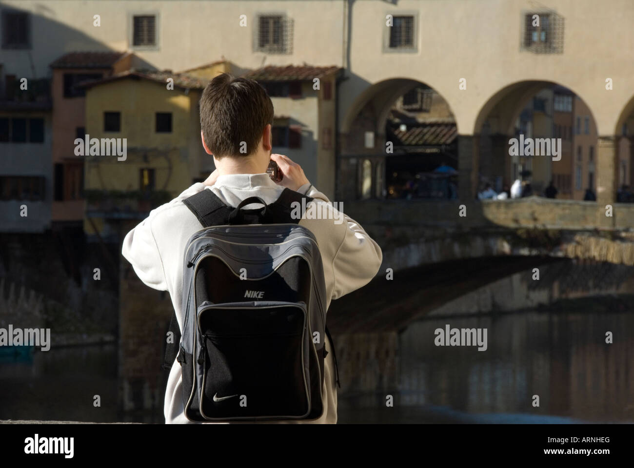 Young backpacker tourist photographing one of the world's most famous sites, the Ponte Vecchio in Florence, - Stock Image
