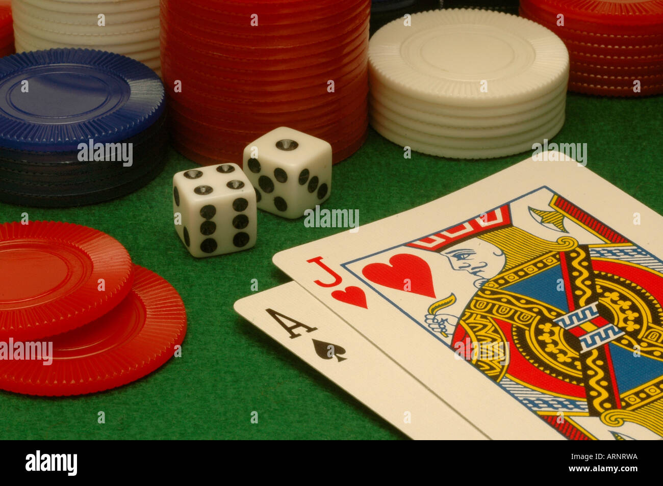 Cards dice and chips on a green felt gambling table. - Stock Image