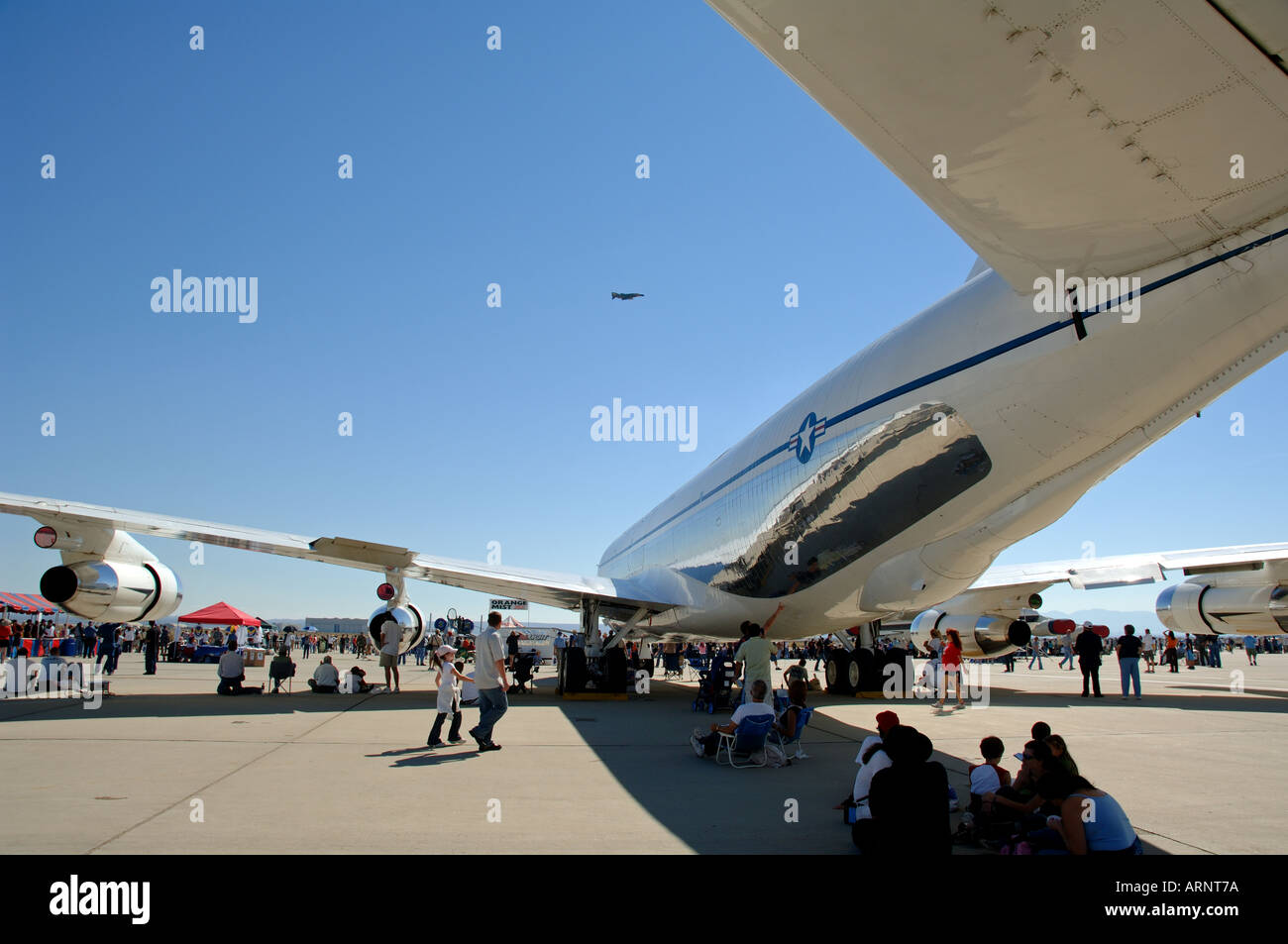 People resting under the fuselage of airplane at Edwards Air