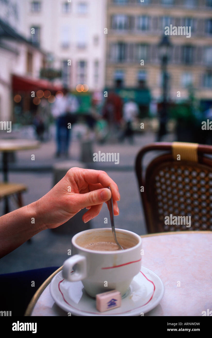 France, Paris, cafe with woman's hand stirring coffee - Stock Image