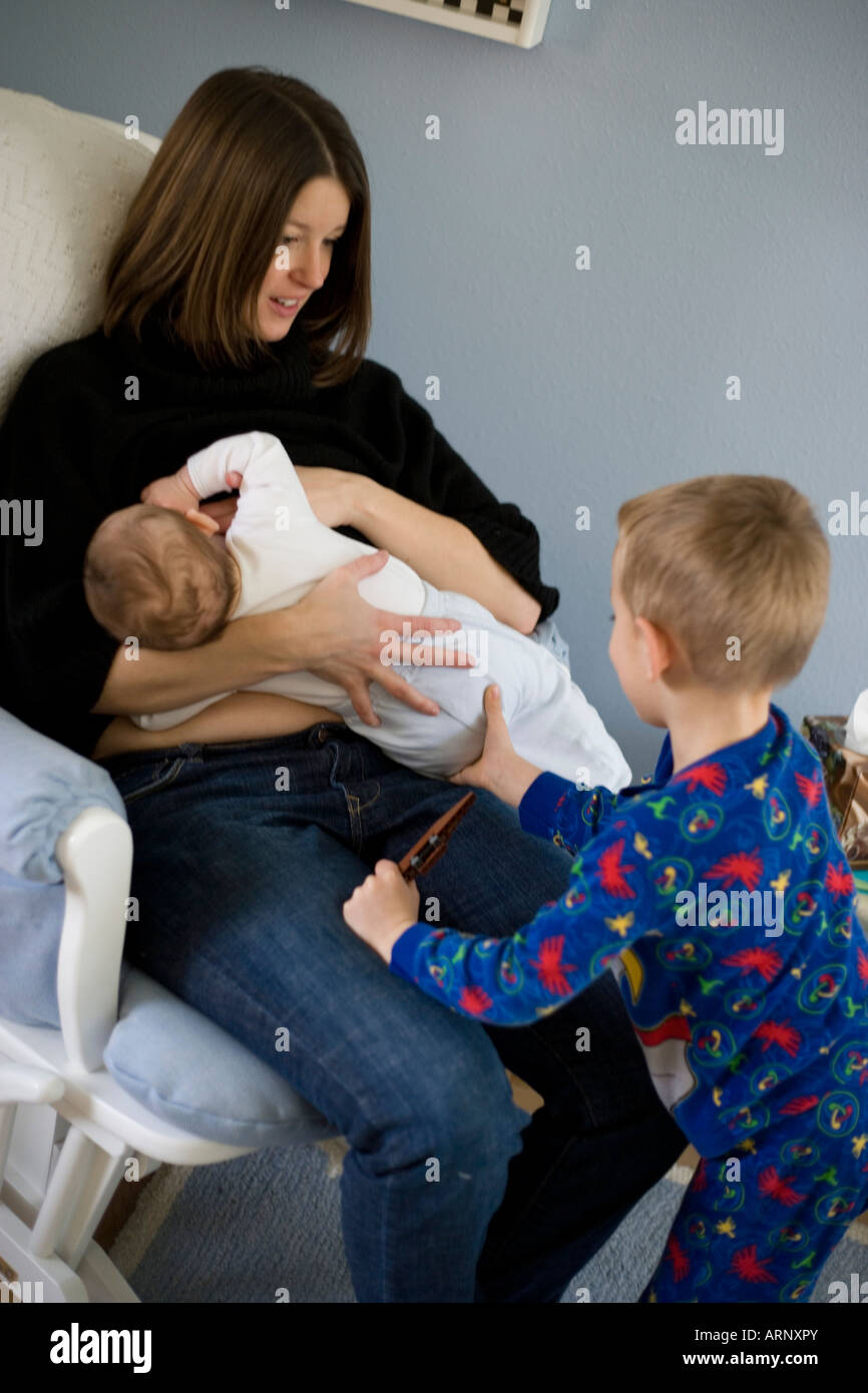 three year old boy trying to get attention from mother while she is nursing her newborn baby - Stock Image
