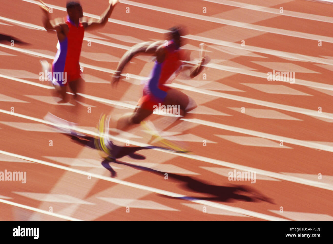 Two runners of a relay team pass the baton. - Stock Image