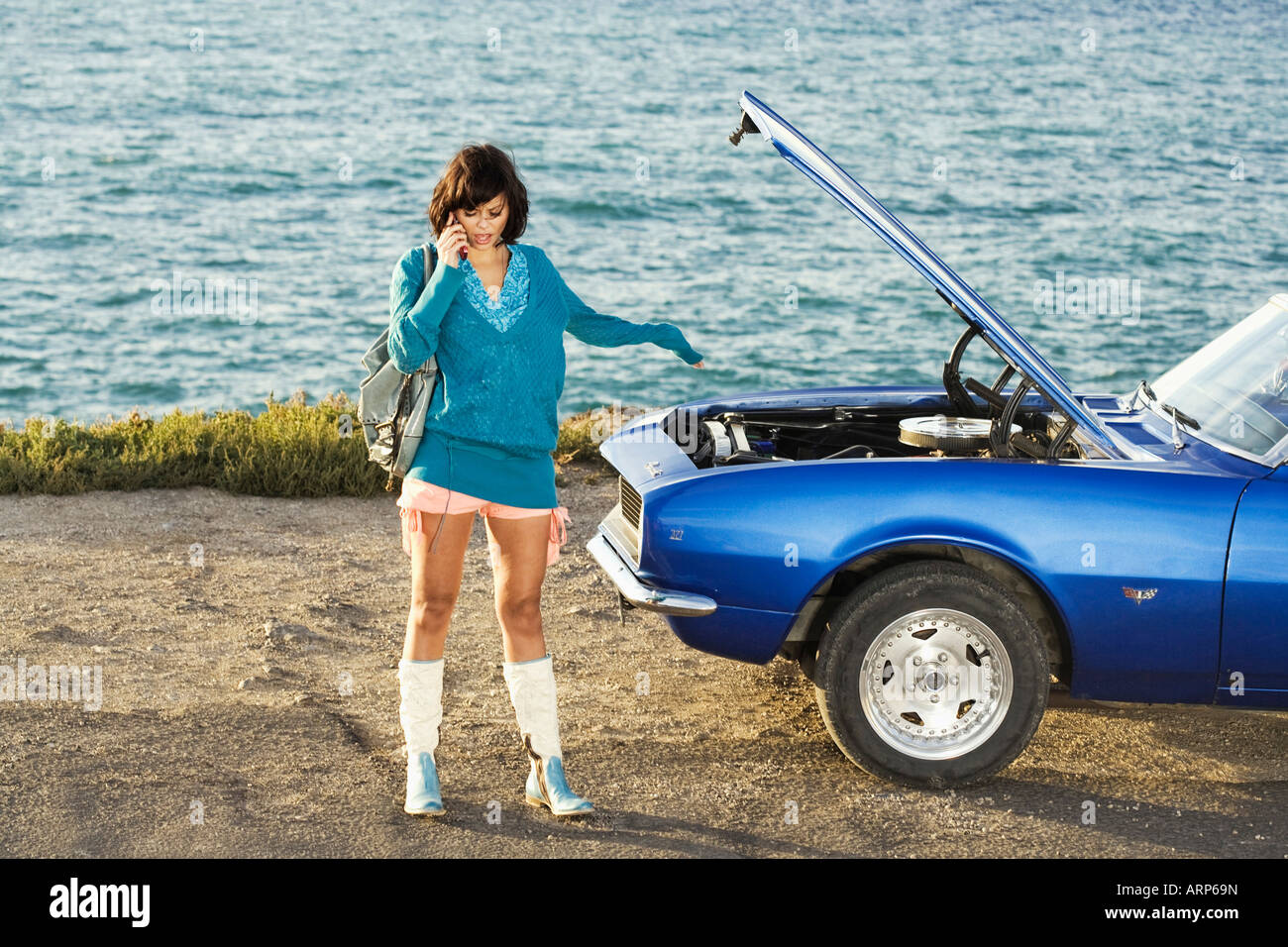 Woman on mobile phone by broken down car - Stock Image