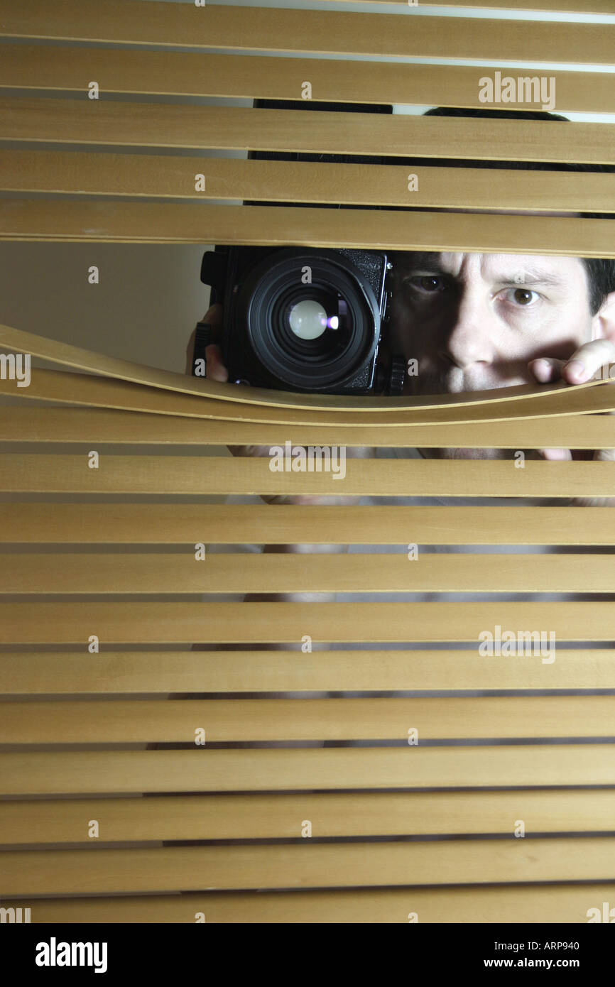 Man looks through blinds with camera - Stock Image