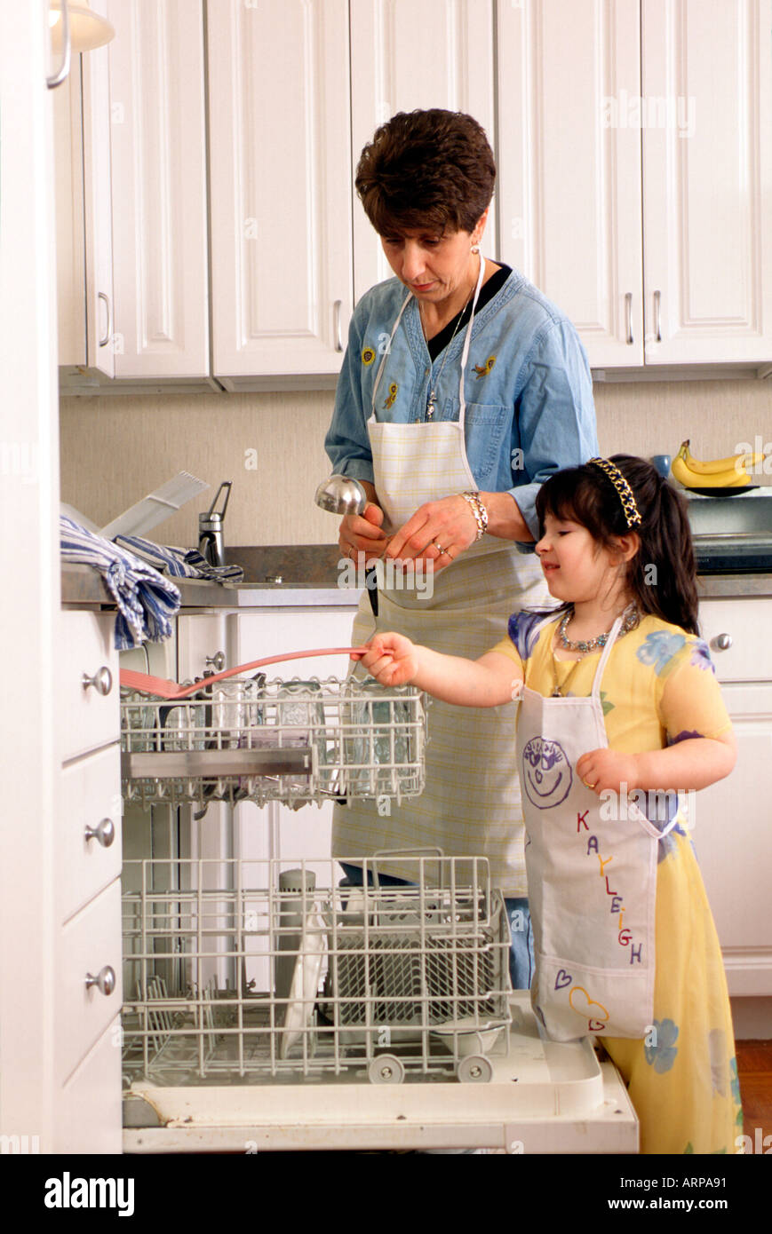 Nanny and 4 1 2 year old put away dishes after baking cookies - Stock Image