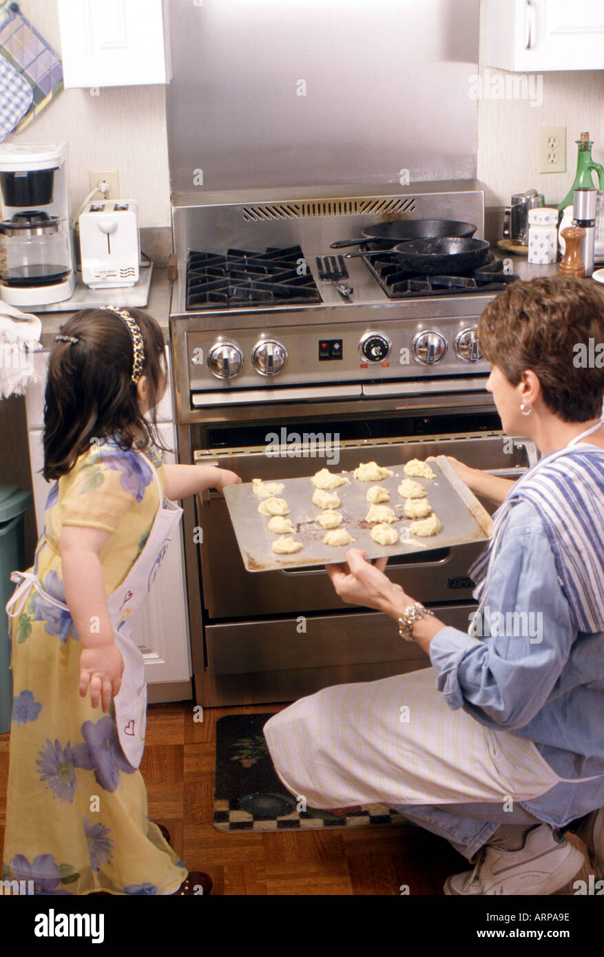 Nanny and 4 1 2 year old girl bake cookies - Stock Image