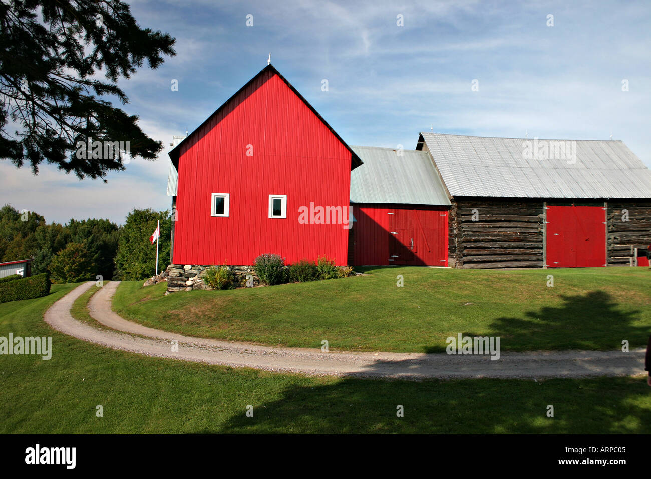 Red Barn A newer red barn joined to an older log barn A rutted laneway passes in front - Stock Image