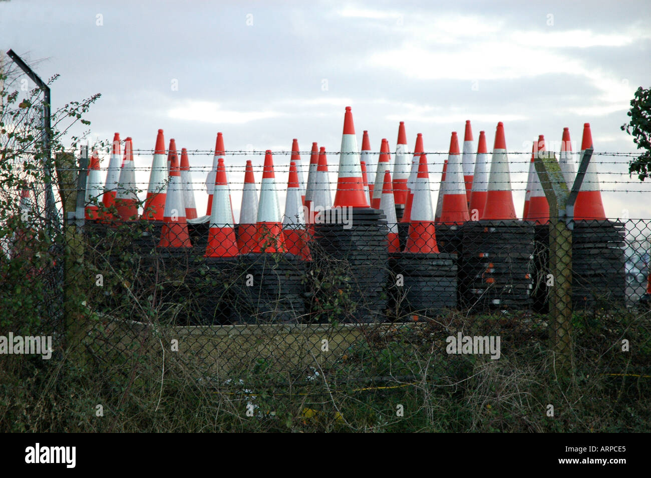 Traffic cones stacked behind fence - Stock Image