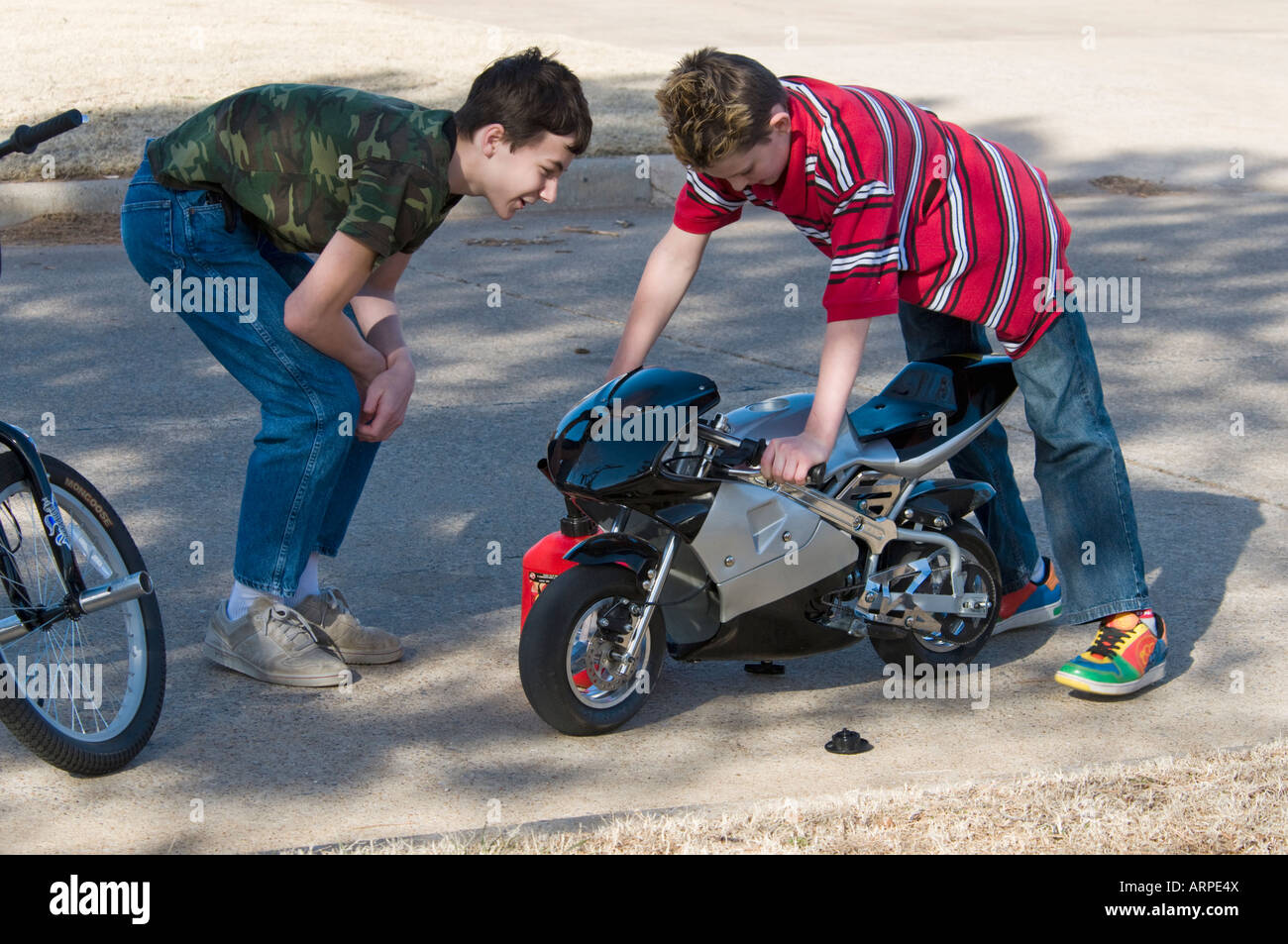 Two teenage boys study a motorized pocket bike that has quit running. - Stock Image