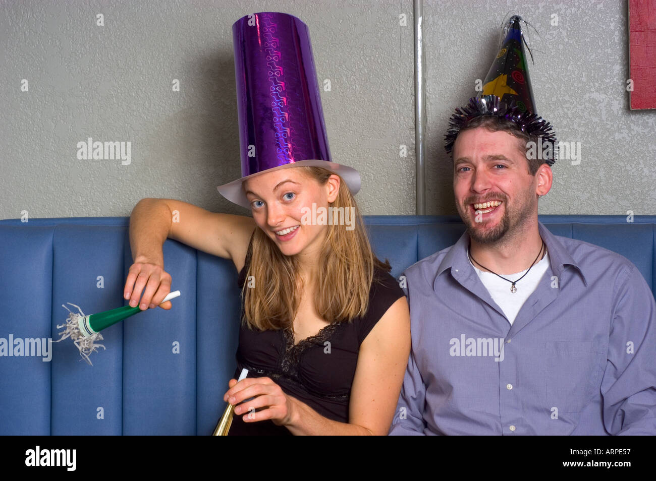 Two young people in party hats with noisemakers looking at camera. - Stock Image