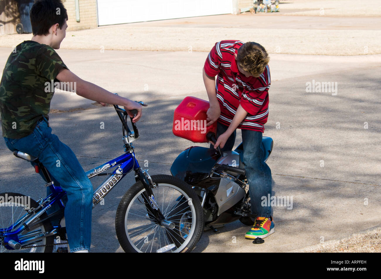 A teenage boy sits on his bicycle and looks on as his friend refruels his motorized pocket bike. - Stock Image