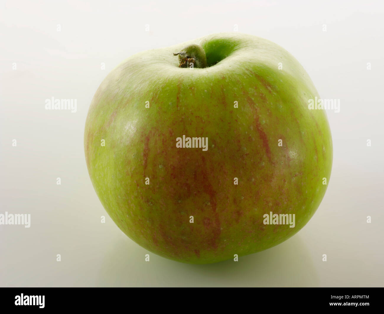 organic British Bramley apple - Whole against white - Stock Image