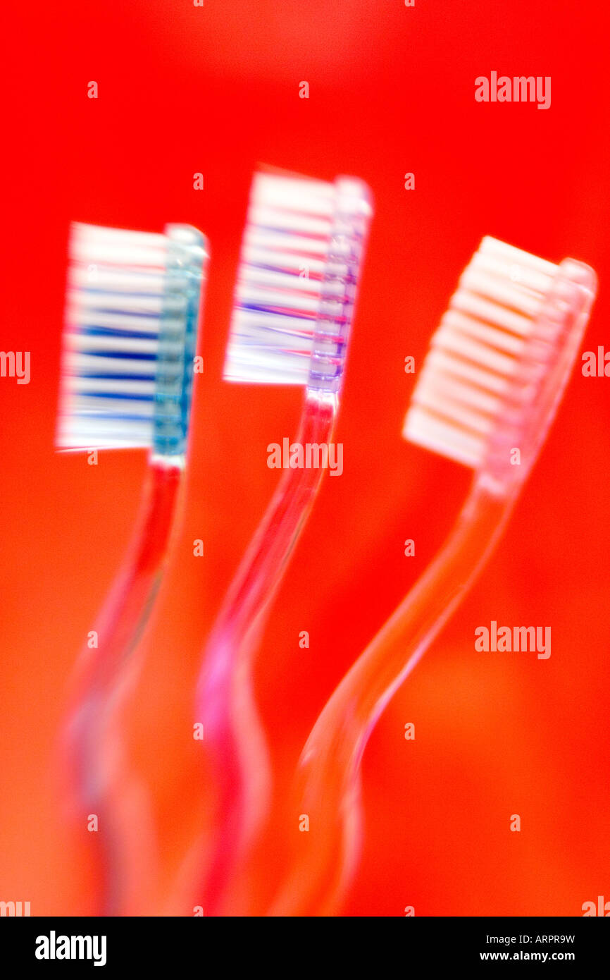 Three toothbrushes against a red background - Stock Image