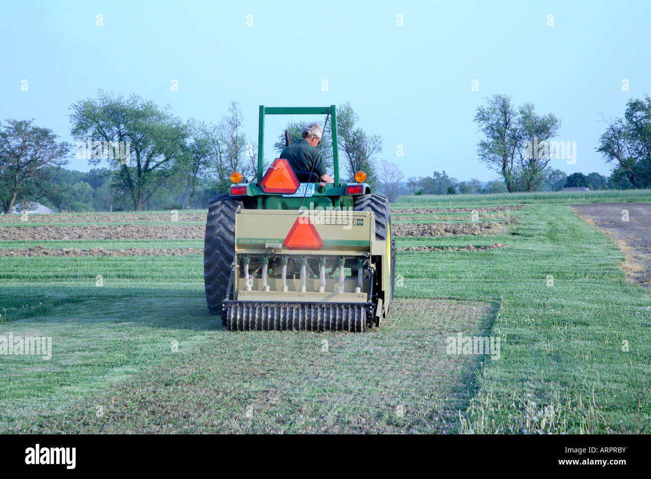 Man driving tractor pulling a slitting seeder. - Stock Image