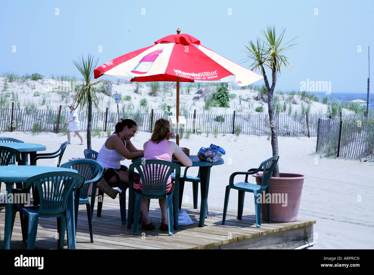 Two Young Women Sitting At Plastic Patio Table Under Red And White